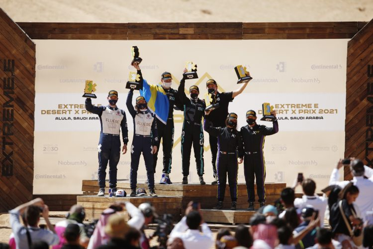 ALULA, SAUDI ARABIA - APRIL 04: Timmy Hansen (SWE), Andretti United Extreme E, Catie Munnings (GBR), Andretti United Extreme E, Johan Kristoffersson (SWE), Rosberg X Racing, Molly Taylor (AUS), Rosberg X Racing, Cristina Gutierrez (ESP), X44, and Sebastien Loeb (FRA), X44, celebrate on the podium during the Desert X-Prix at AlUla on April 04, 2021 in AlUla, Saudi Arabia. (Photo by Zak Mauger / LAT Images)